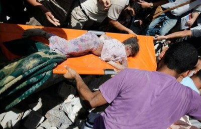 Medics remove a child from the rubble after the Israeli airstrike in Shaati camp today